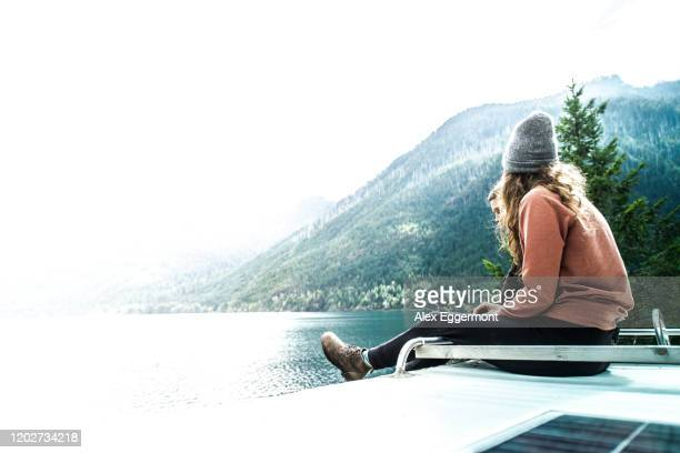 woman seated on top of campervan overlooking the lake, cathedral grove, british columbia, canada - grove_(nature) stock pictures, royalty-free photos & images