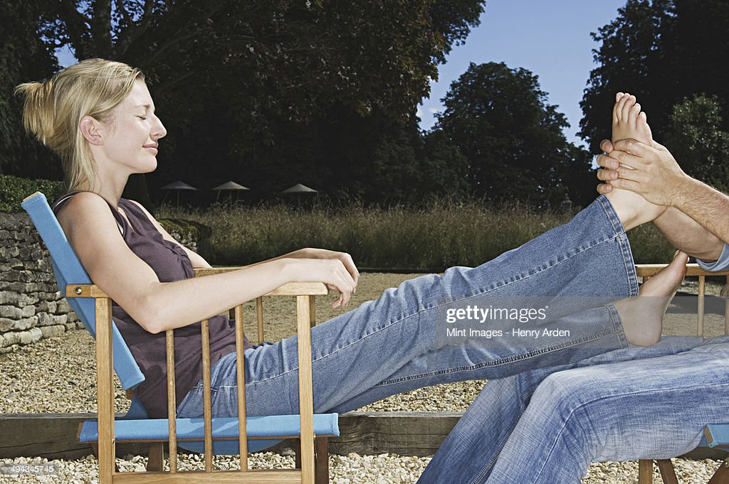 A woman seated with her legs outstretched, having a foot massage. : Stock Photo