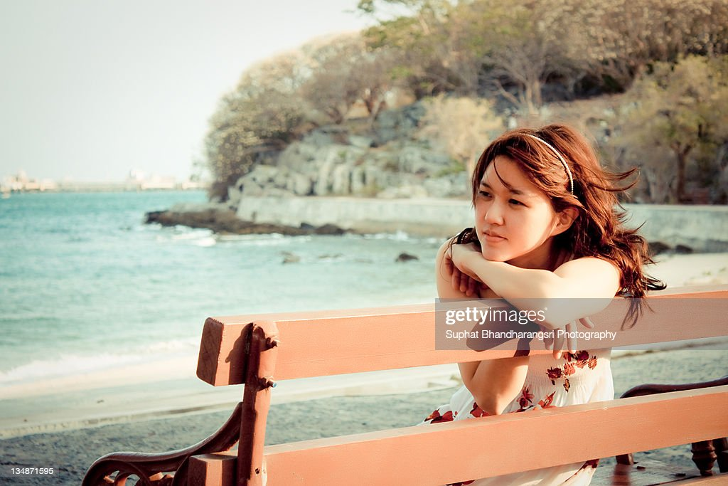 Woman seating on bench by beach : Stock Photo