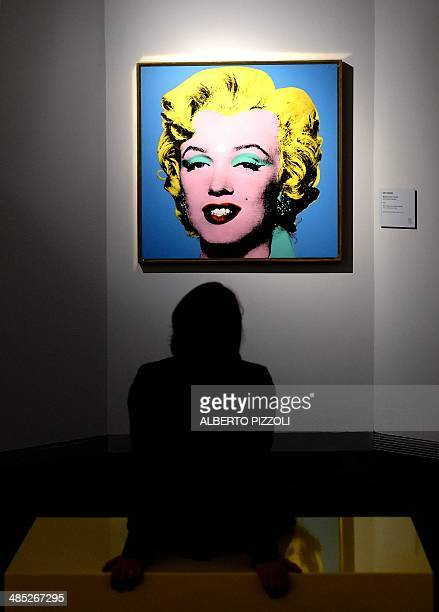 A woman seats in front of 'Blue Shot Marilyn' a painting by US artist Andy Warhol as part of the exhibition 'Warhol' on April 17 2014 in Rome The...