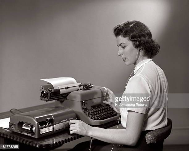 Woman Secratary Typing Dictation From Dictaphone Indoor.