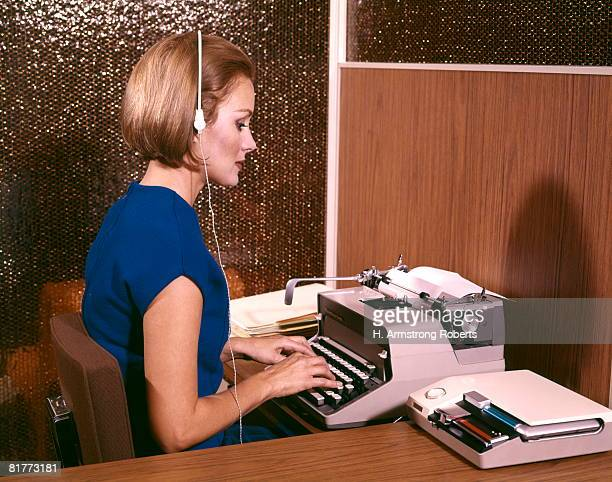 Woman Secretary Typing Typewriter Listening To Dictation On Tape Recorder Earphones Headset Desk.