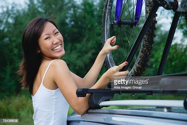 Woman securing bike on top of car, smiling at camera