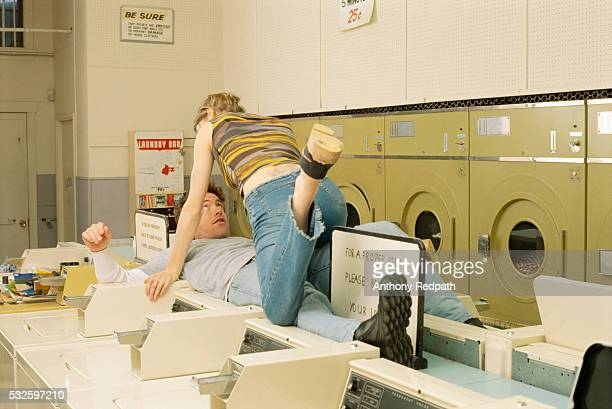 woman seducing man in laundromat - seduction stock pictures, royalty-free photos & images
