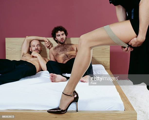 woman seducing two men - men wearing stockings stock photos and pictures