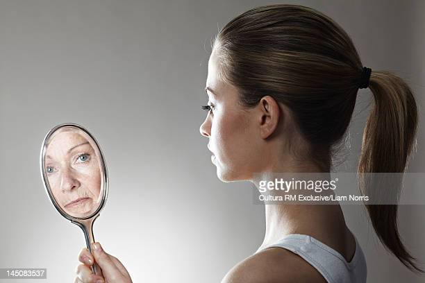 Woman seeing herself older in mirror