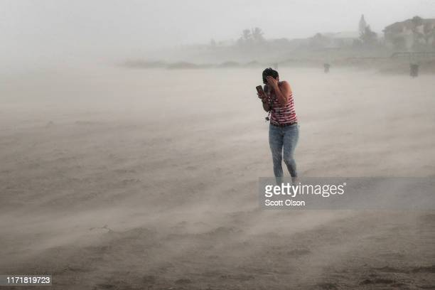 A woman seeks cover from wind blowing sand and rain whipped up by Hurricane Dorian as she walks on the beach on September 2 2019 in Cocoa Beach...