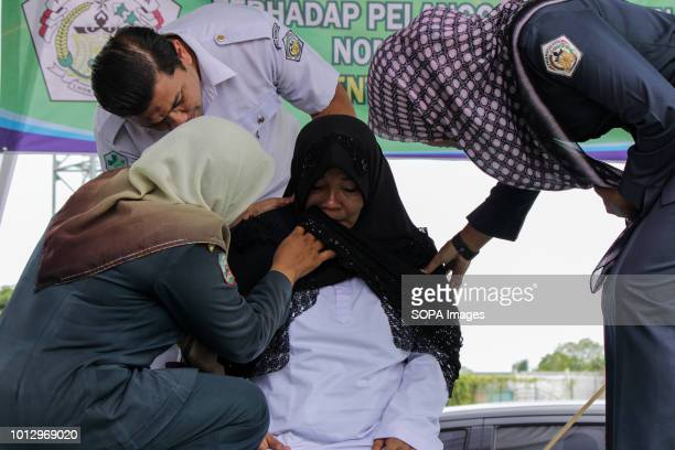 LHOKSEUMAWE ACEH INDONESIA A woman seen crying after being whipped on the public stage Four people were convicted by the Lhokseumawe Sharia Court of...