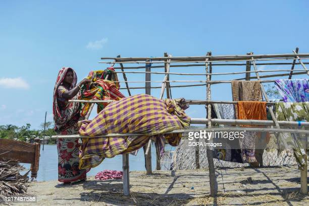 Woman seen drying her clothes on her temporary house in the aftermath of the extremely severe cyclonic storm Amphan. Thousands of shrimp enclosures...