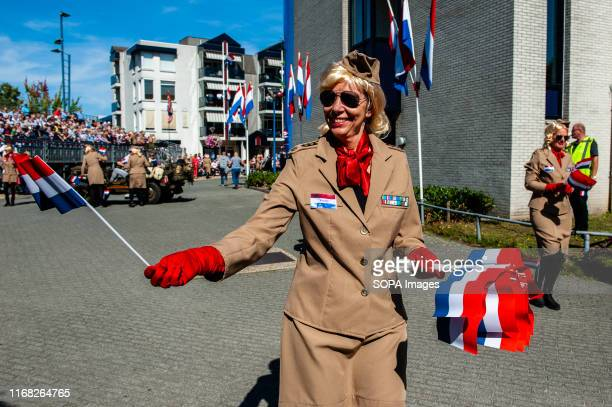 A woman seen giving out Dutch flags during the parade The 2019 commemorating 75 years since Operation Market Garden took place Operation Market...