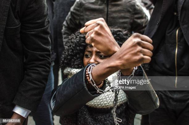 A woman seen having her hands chained as a sign of protest during the demonstration against slavery in Libya Around 300 people have demonstrated...