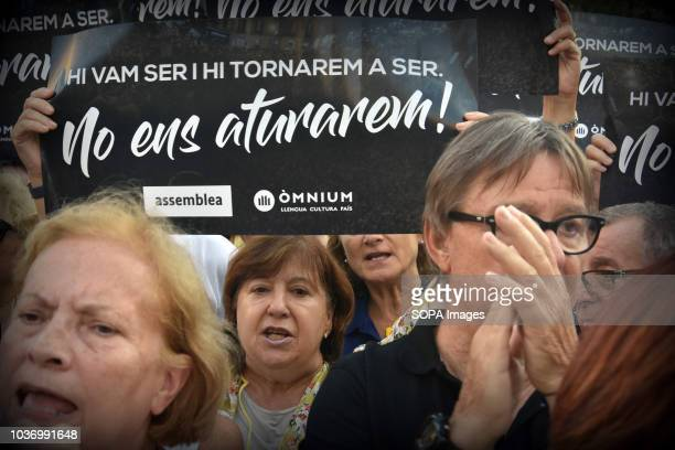 A woman seen holding a banner as they gather at the Economy headquarters during protests in support of Catalonia's independence and commemorate the...
