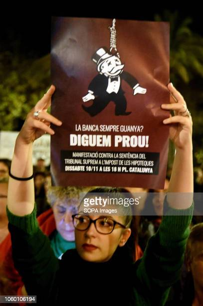 A woman seen holding a placard saying Banking always wins enough is enough during the demonstration against the Spanish Supreme Court decision of...