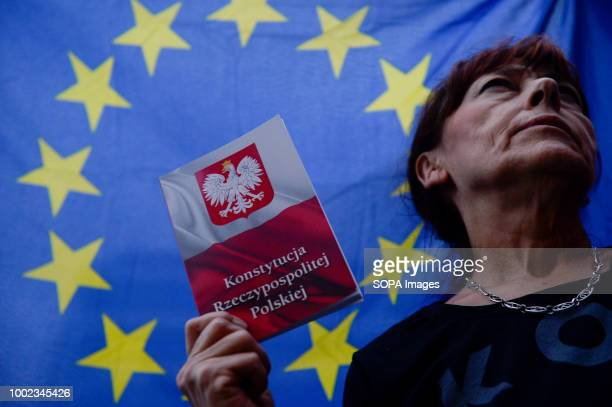 A woman seen holding a polish constitution with a European Union flag in the background during the protest People demonstrate against reforms of the...