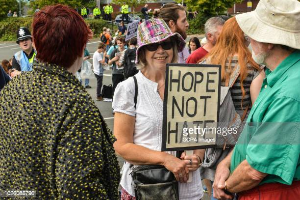 A woman seen holding a poster during a counter protest They were part of a counter protest in opposition to a march organized by the far right the...