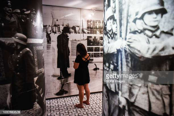 A woman seen reading about daily life in Krakow during Nazi occupation during the exhibition Exhibition at Oskar Schindler's Enamel Factory museum it...