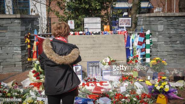 A woman seen reading condolence messages during the annual memorial service at the Hillsborough Hundreds of people gather outside the football ground...