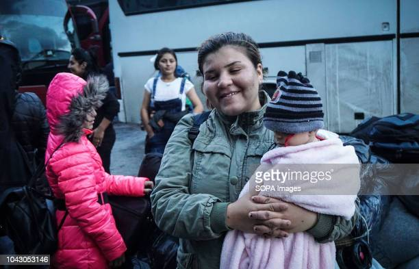 A woman seen standing carrying a kid during their arrival at the port 400 migrants and refugees were transferred upon their arrival from the island...