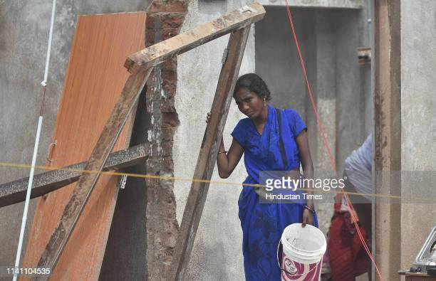 A woman seen standing near her damaged house on May 4 2019 in Puri India At least 12 people are reported to have died and more than a thousand others...