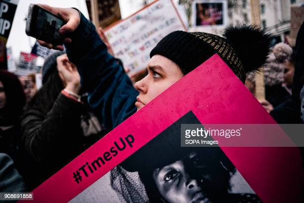 A woman seen taking a photograph of the demonstration during the march Scores of women across the United Kingdom took to the streets on Sunday to...