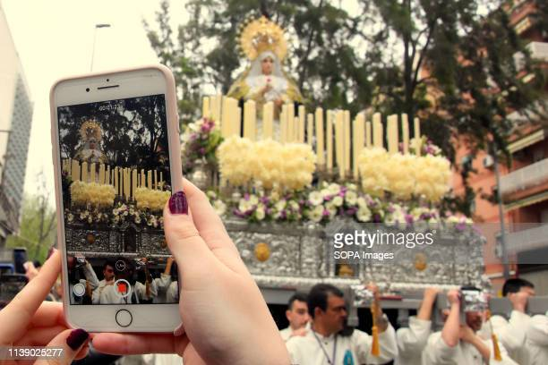 L´HOSPITALET CATALONIA SPAIN A woman seen taking pictures of the Virgin of Remedies on her smartphone during the parade Easter Parade 2019 Hospitalet...