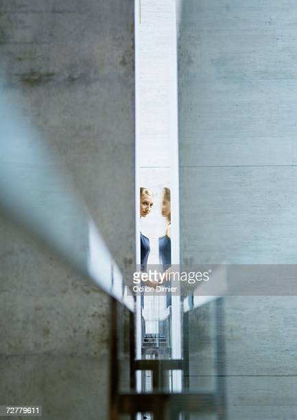Woman seen through narrow opening, with reflection
