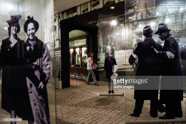 A woman seen walking through glass displays during the exhibition Exhibition at Oskar Schindler's Enamel Factory museum it is primarily a story about...