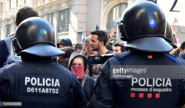 A woman seen with her face covered by a handkerchief between two Catalan policemen during the protest Clashes between proindependence protesters and...