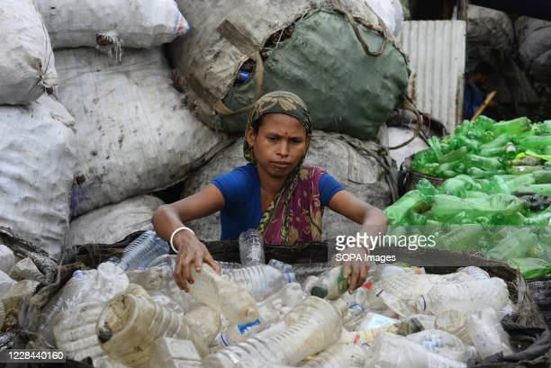 Woman seen working at a plastic bottle recycling factory besides the river Buriganga in Dhaka. Dhaka is getting back to its normal life after months...