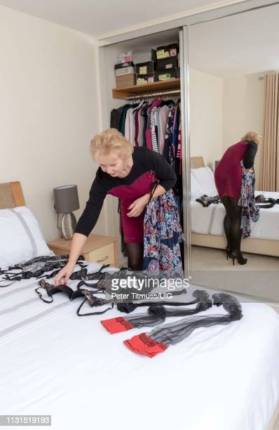 woman selecting clothes from her wardrobe in bedroom with full length mirror - female flasher stock pictures, royalty-free photos & images