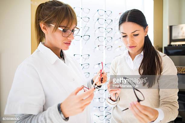 Woman selecting eyeglasses in optical shop