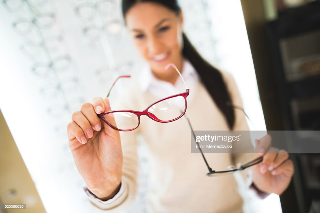 Woman selecting eyeglasses in optical store : Stock Photo