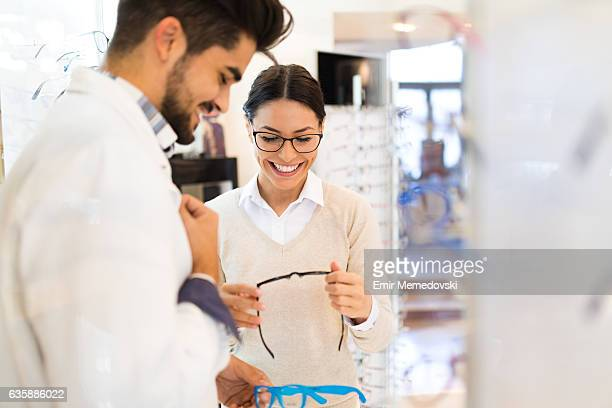 woman selecting eyeglasses in optical store - optometry stock photos and pictures