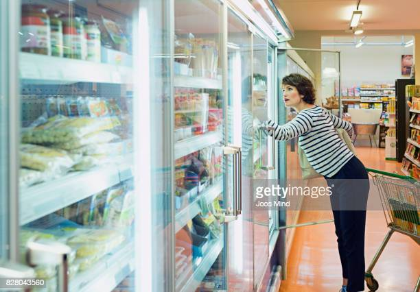 woman selecting frozen food in supermarket