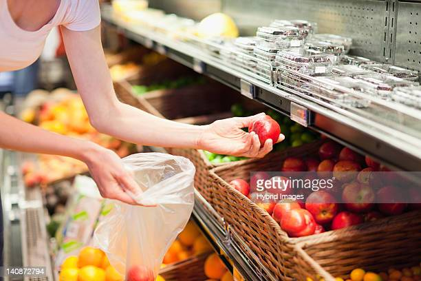 Woman selecting fruit at grocery store