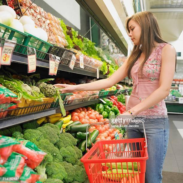 Woman selecting produce at supermarket