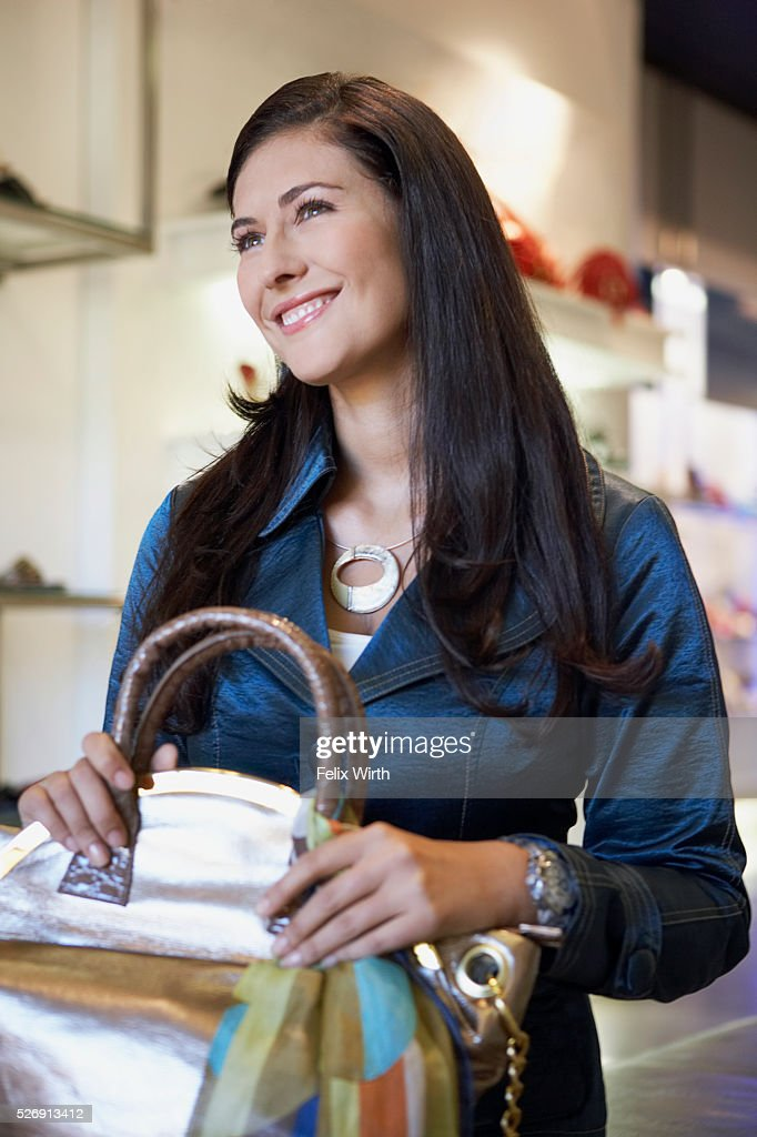 Woman selecting purse in boutique : Stock-Foto