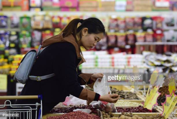A woman selects dried longan at a supermarket in Fuyang in eastern China's Anhui province on February 9 2018 China's factory inflation eased to a...