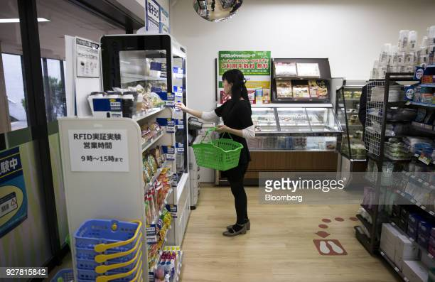 A woman selects items from a shelf during a demonstration of an unmanned cash register at a FamilyMart UNY Holdings Co FamilyMart convenience store...