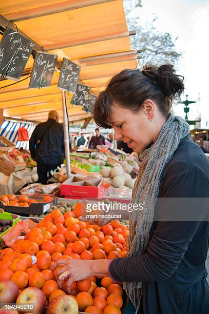 Woman selects tangerines from a market stall.