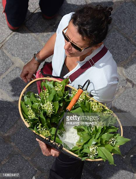 A woman sell sprigs of lily of the valley during the annual May Day workers' march on May 1 2012 in Lyon centraleastern France Both candidates for...