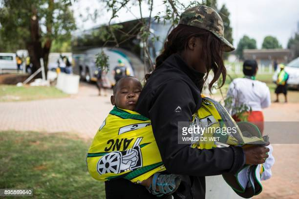 A woman selling African National Congress branded goods carries her sleeping baby in an ANC flag on the last day of the 54th ANC national conference...