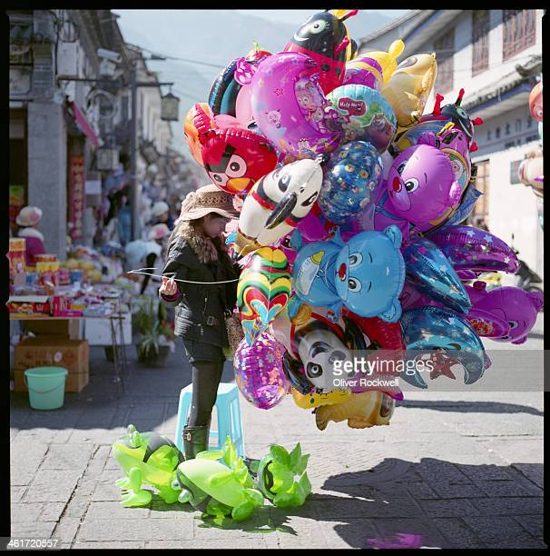 CONTENT] A woman selling balloons at a busy crossroad in the old town of Dali Yunnan Province China