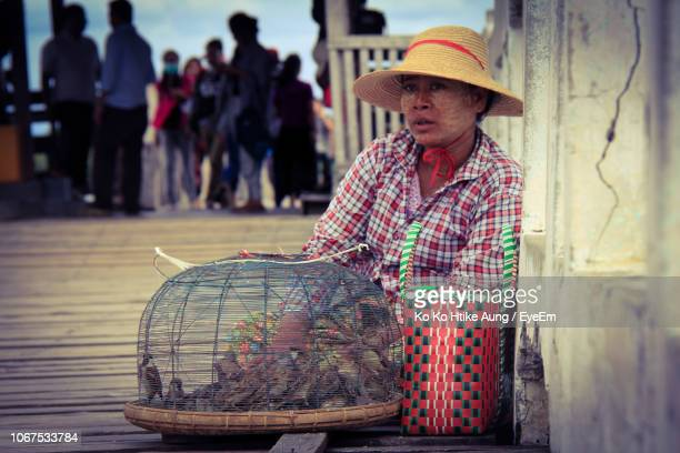 woman selling bird while sitting on footpath - ko ko htike aung stock pictures, royalty-free photos & images