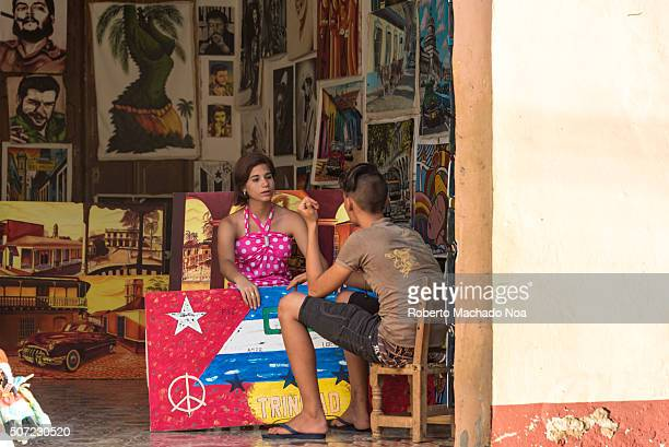 Woman selling canvas paintings at store and chatting with a young man The store has various portraits and paintings related to the personalities and...