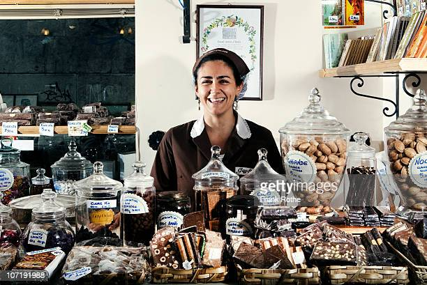 woman selling chocolate in a chocolare shop - chocolate shop stock pictures, royalty-free photos & images