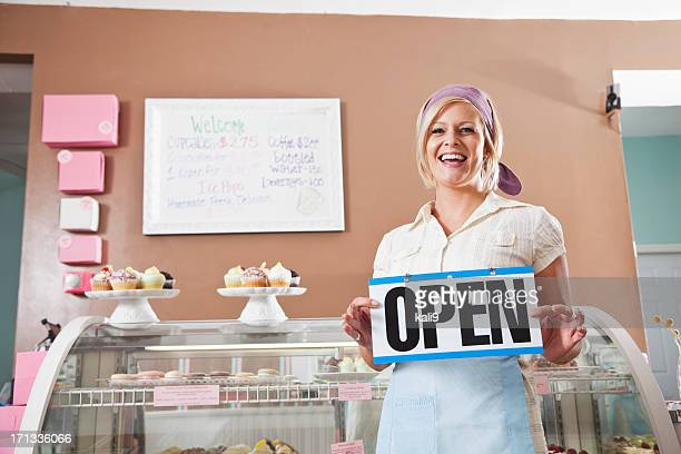 Woman selling cupcakes, holding open sign