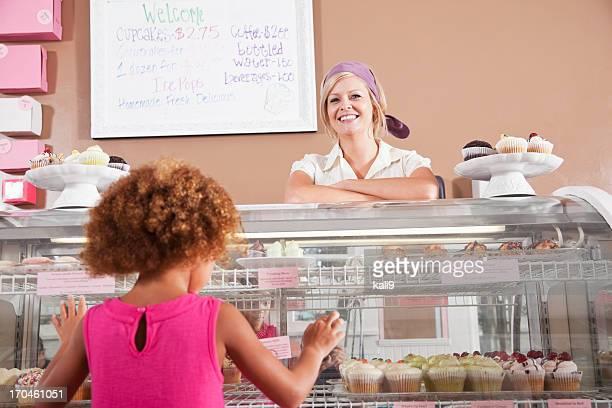 Frau verkaufen cupcakes für kleine Mädchen