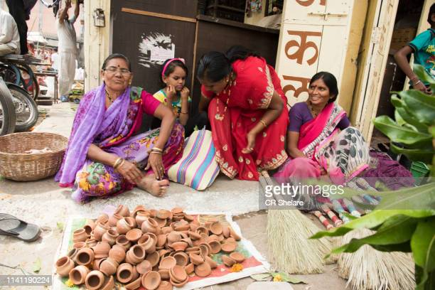 woman selling diwali diya or clay pot on street. - {{asset.href}} imagens e fotografias de stock