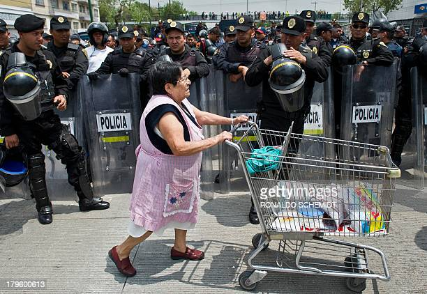 A woman selling food passes in front of police officers standing guard as teachers who protest against an education reform hold roadblocks in the...